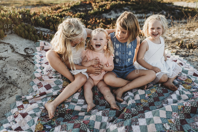 Four sisters sitting on blanket at beach laughing at sunset