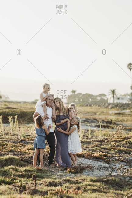 Lifestyle portrait of family with young girls smiling at beach sunset