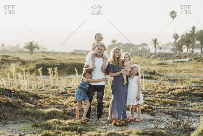 Traditional portrait of family with young girls smiling at beach sunset