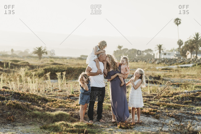 Lifestyle portrait of family with young girls kissing at beach sunset