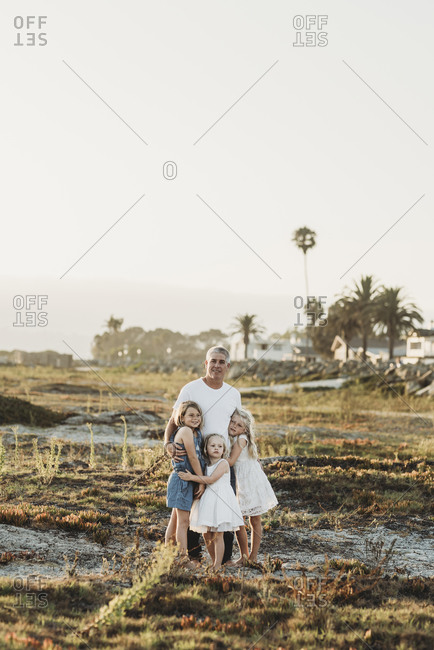 Traditional portrait of father with young sisters smiling at beach
