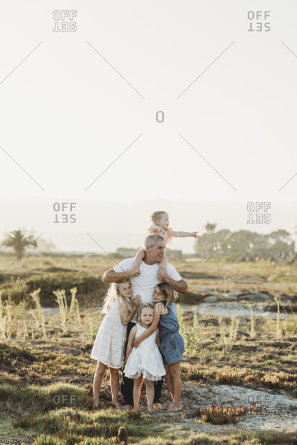 Lifestyle portrait of dad with young girls smiling at beach sunset