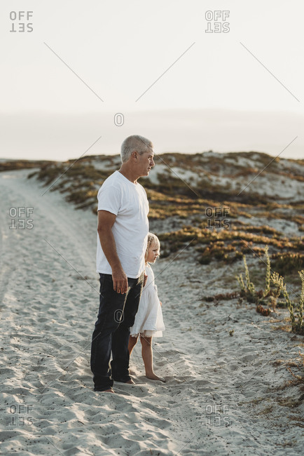 Father and preschool aged girl standing in sand at beach looking away