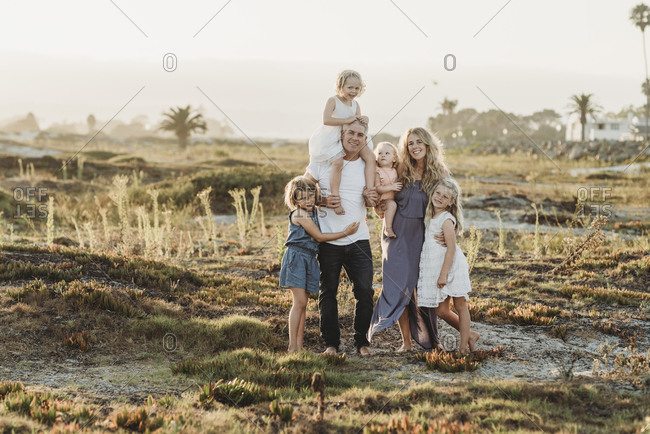 Portrait of family standing in sand at beach during sunset smiling