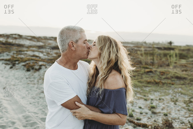 Husband and wife embracing and kissing at beach during sunset
