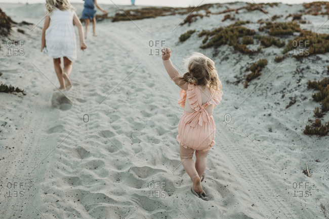 Young toddler girl chasing big sisters at beach during sunset