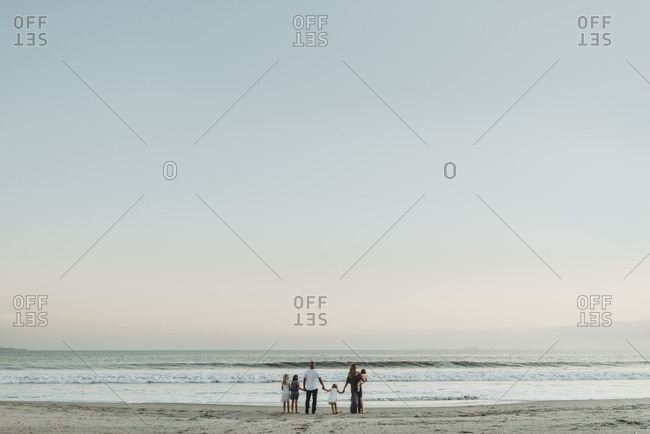 Landscape view of young family standing in ocean at sunset