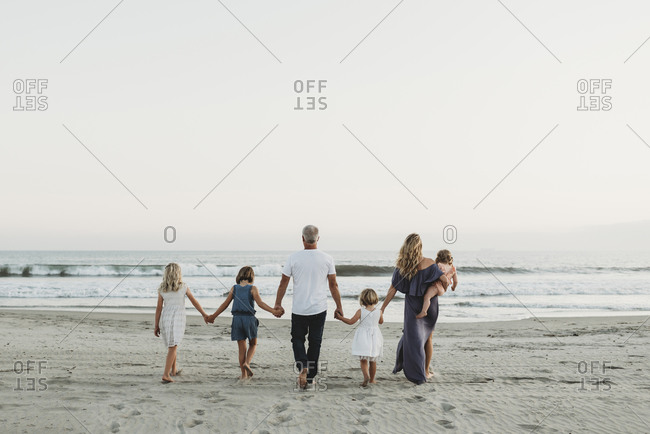 Behind view of young family walking towards the ocean at sunset