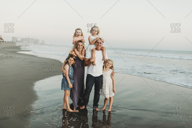 Traditional portrait of family with four children smiling at beach sun