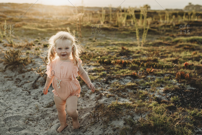 Portrait of toddler girl with pigtails smiling at camera at beach