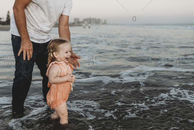 Toddler girl splashing in ocean with father at sunset