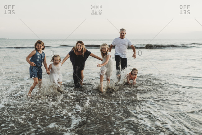 Family with four girls playing and splashing in waves at sunset