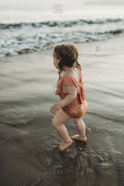 Young toddler girl with pigtails walking into the ocean