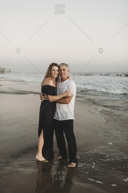 Traditional portrait of married couple standing in ocean at sunset