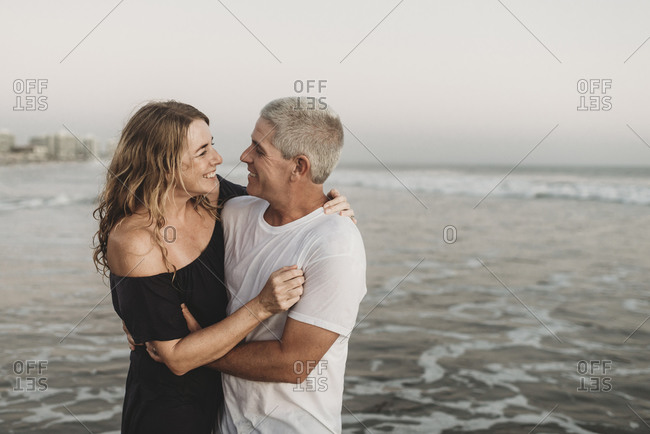Side view of married couple looking at each other in ocean