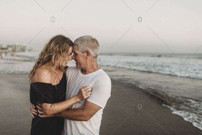 Side view of married couple embracing each other in ocean