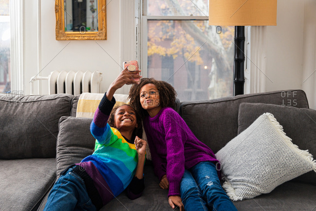 Smiling girl taking selfie with sister while leaning on sofa at home