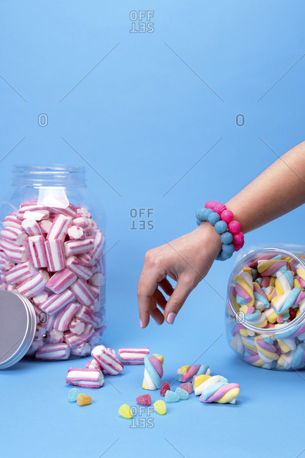 Female hand using chopsticks with candy sushi