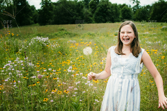 Girl Laughing as She Picks Wild Flowers in a Field