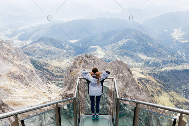 Millennial girl enjoys the views of Alps from the observation deck