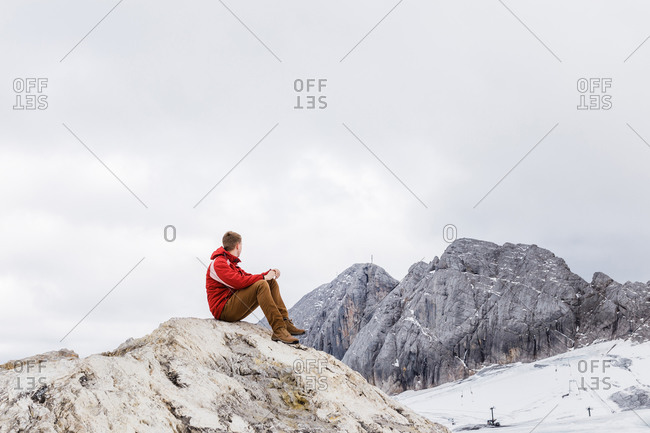Young millennial man enjoys the views of the Alps standing on glacier