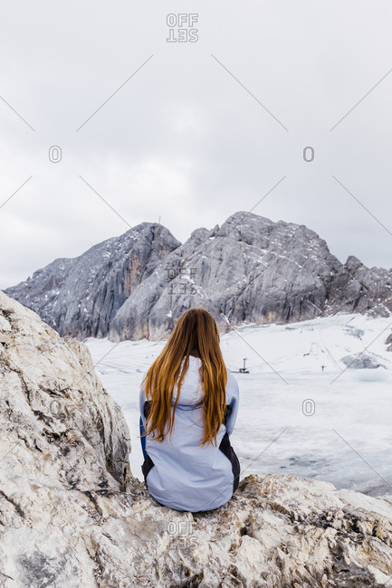 Young millennial girl enjoys the views of the Alps standing on glacier