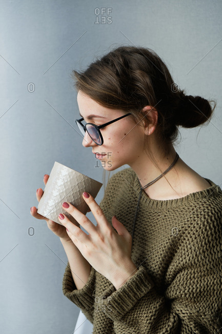 Millennial brown-haired girl in glasses drinking tea with cakes alone