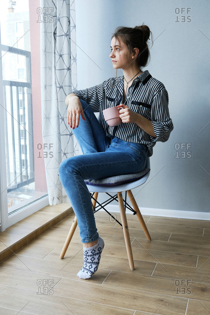 Millennial brown-haired girl drinking tea with cakes alone