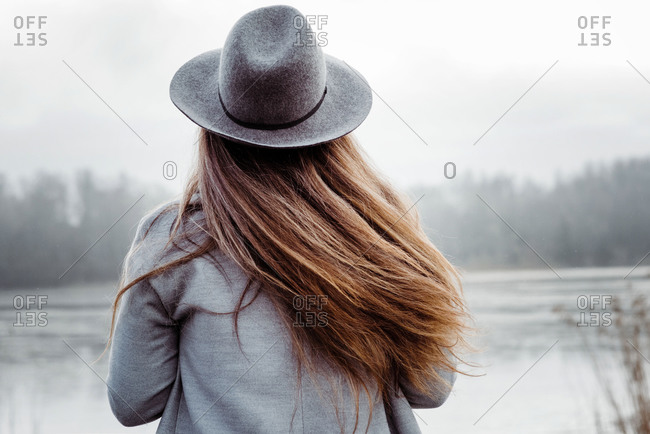 The back of a woman's hair blowing in the wind at the beach in winter