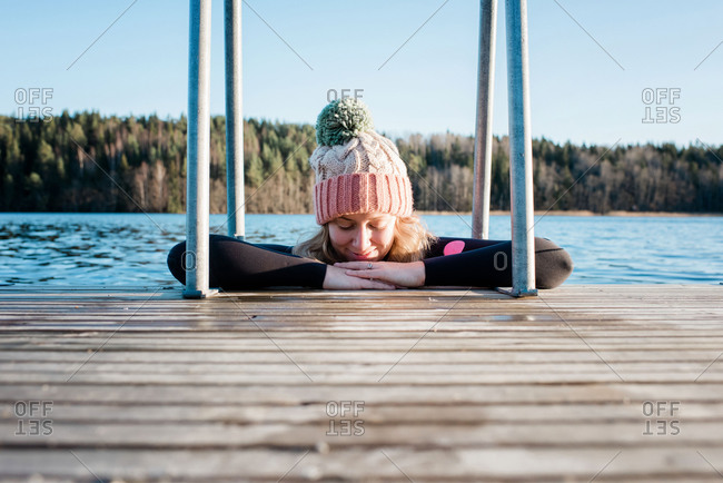 Woman cold water ice swimming in the sea in Sweden leaning on a pier