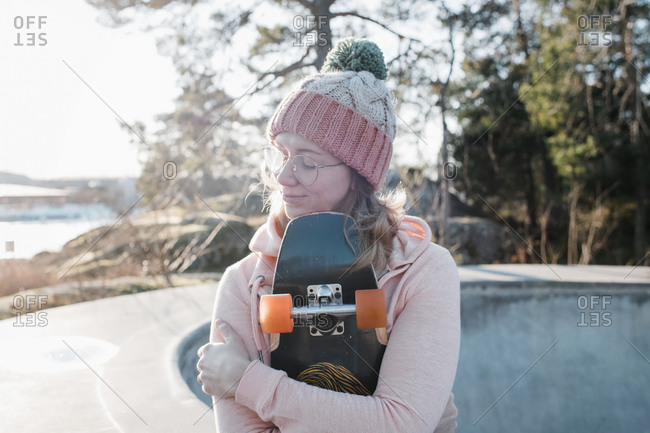 Woman sat with her eyes closed holding her skateboard in a skatepark