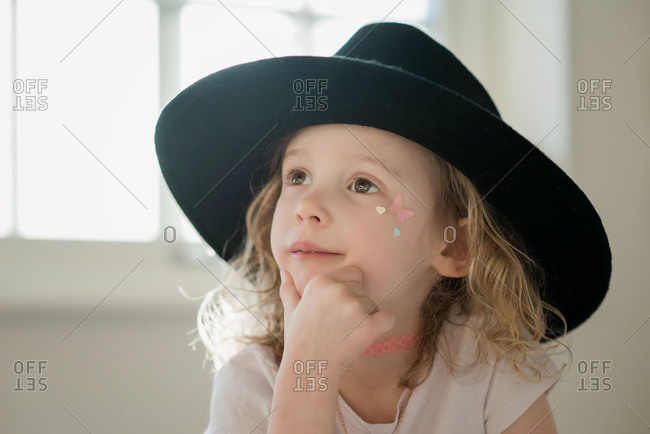 Portrait of a young girl with her face painted and a fancy dress hat
