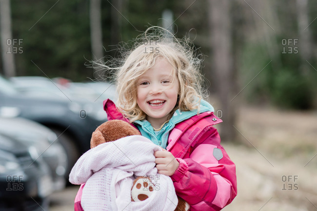 Candid portrait of a young girl smiling  with messy hair and comforter