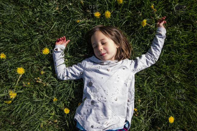 Above-view of peaceful child laying in field of wildflowers in Spring