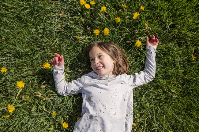 Above-view of a happy smiling child laying in a field of wildflowers