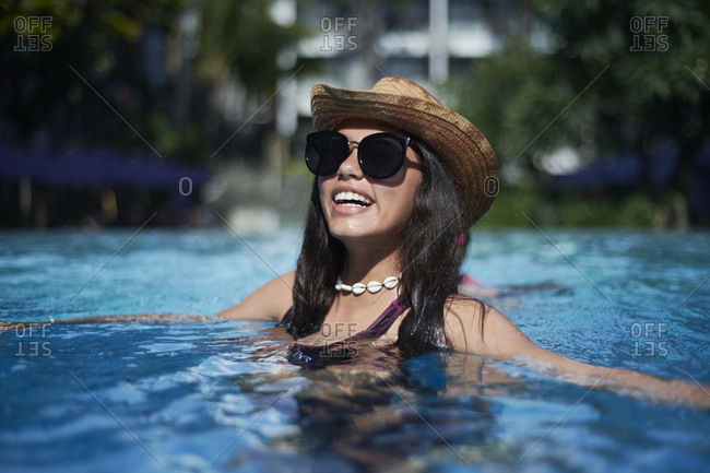 Stylish trendy young teen girl wearing a straw hat and necklace