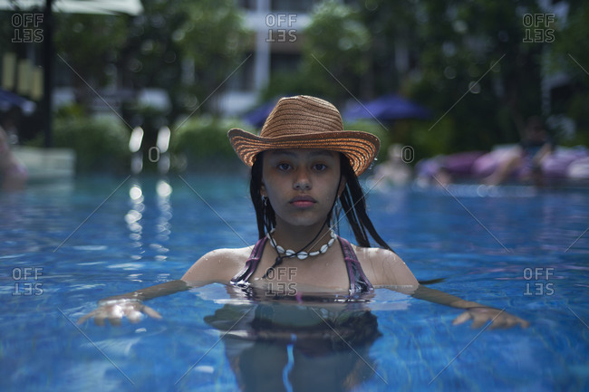 Stylish trendy young teen girl in the pool wearing a straw hat
