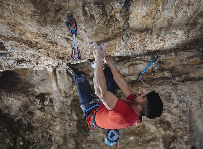 Aerial view of a climber on a hard sport climbing route in a cave.