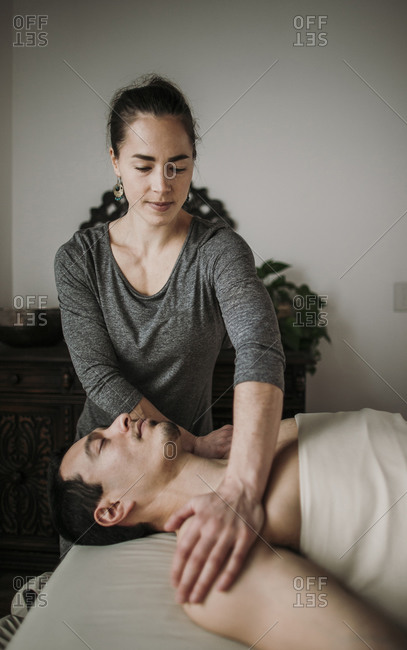 Female massage therapist treats male Hispanic patient