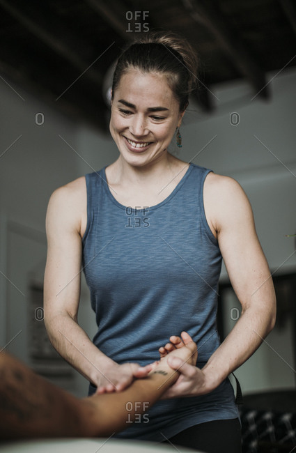 Smiling massage therapist treats her patient's hand and arm