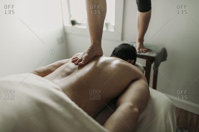 Massage therapist uses her feet to treat male patient's back