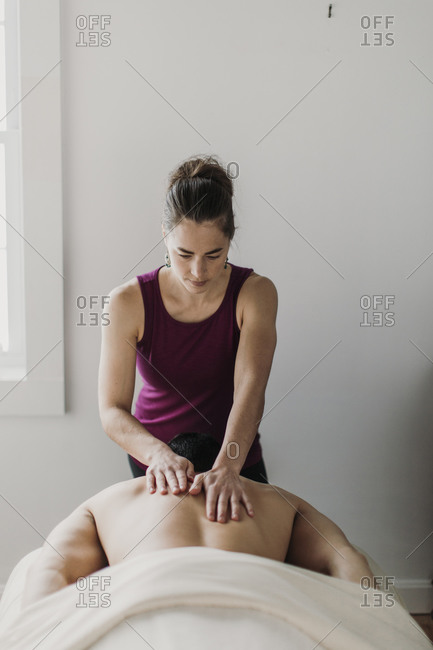 Female massage therapist treats male patient's back with her hands