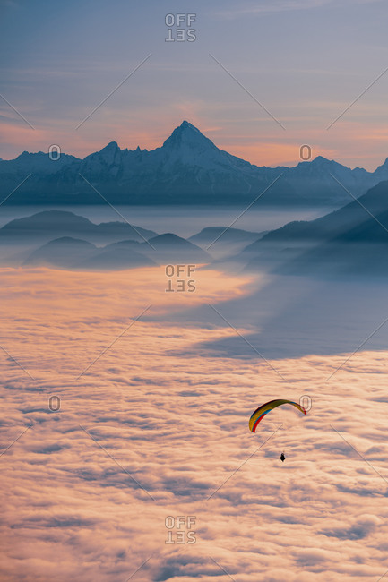 An adventurous sportsman seen paragliding above the clouds at sundown