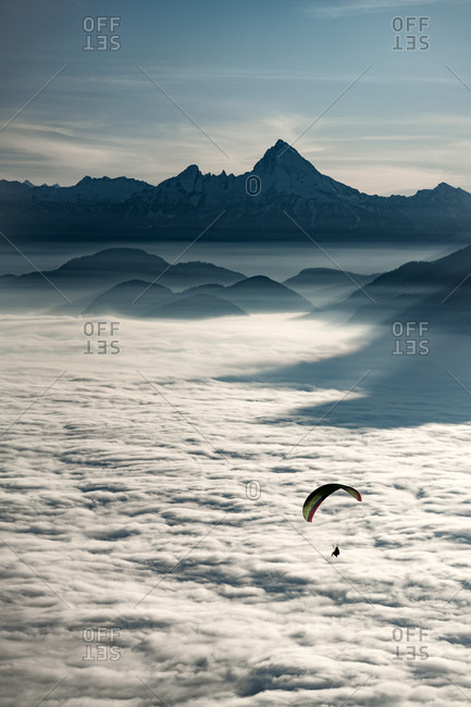 An adventurous sportsman seen paragliding above the clouds in high contrast
