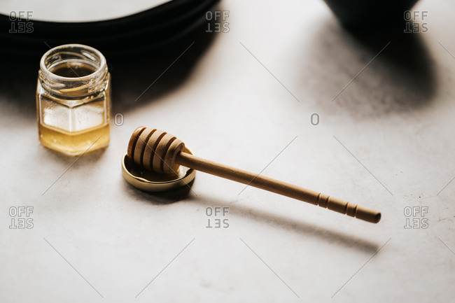 Glass jar of honey and a honey stick on gray surface