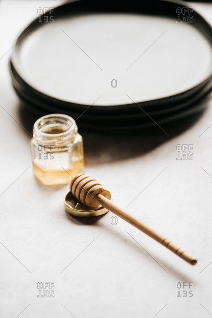 Glass jar with honey and a honey stick on gray surface