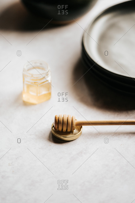 Glass jar with honey and a honey stick on gray surface side view