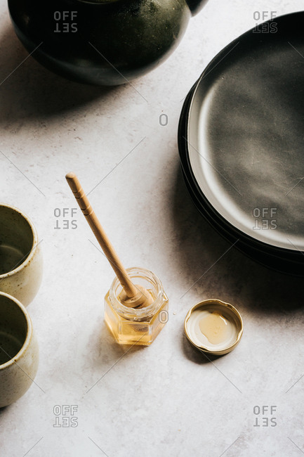 Glass jar with honey and a honey stick on gray surface side view from above