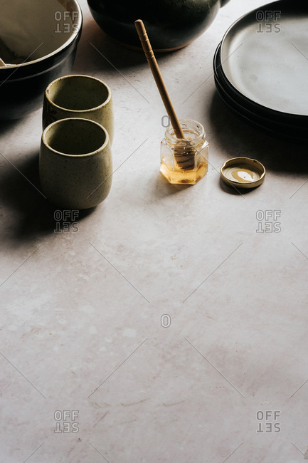 Glass jar with honey and a honey stick on gray surface beside dishes