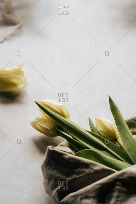 Bundle of spring tulips wrapped in linen cloth